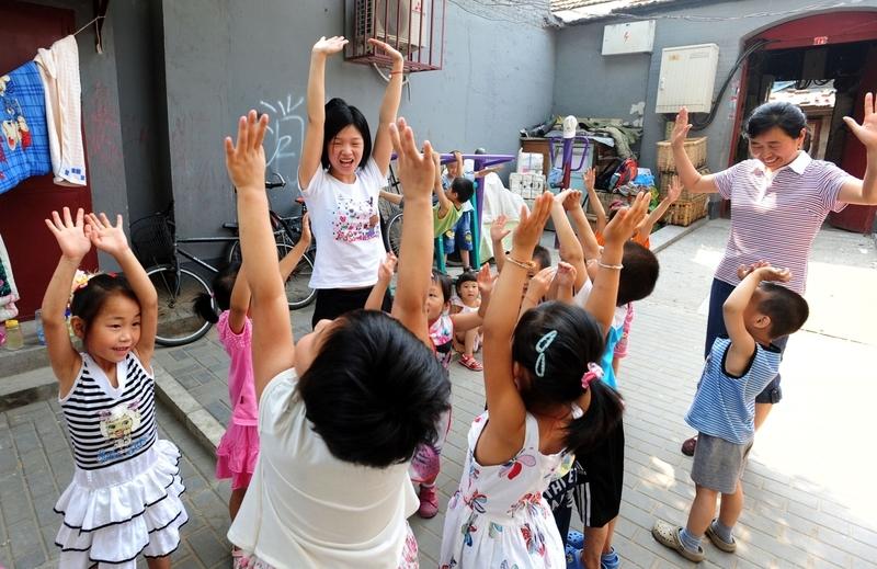 大陸低收入家長負擔不起正規幼兒園大幅上漲的費用,黑幼兒園(非正規幼兒園)應運而生。圖為2010年7月7日,民工子女在北京市場旁一起玩遊戲的景象。(AFP)