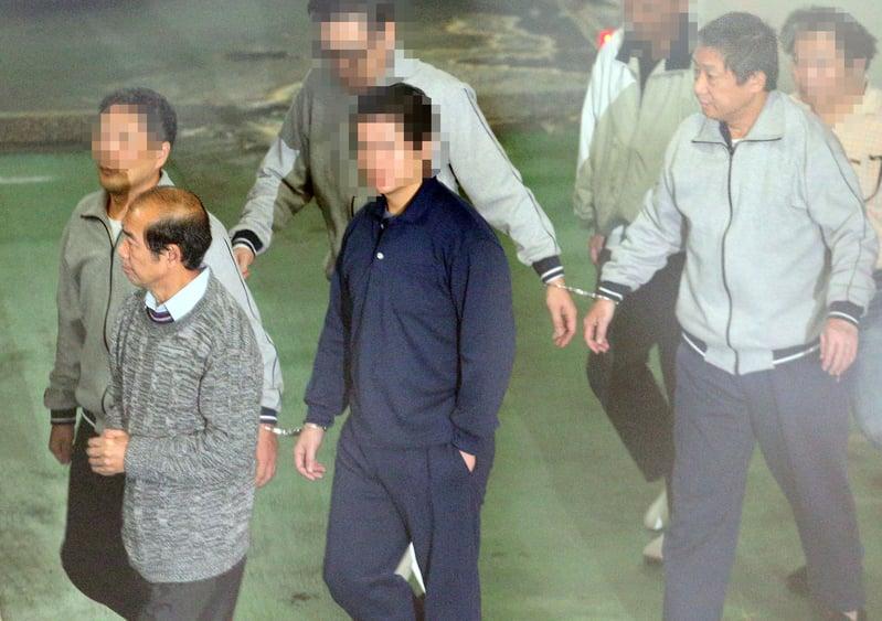 台北地檢署偵辦中國大陸情報份子鎮小江(前右)在台發展組織案,16日提訊在押的鎮小江、退役陸軍少將許乃權(前左)。(中央社)