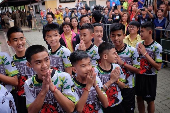 7月18日,被困洞穴18天的泰國小足球隊在獲救後首次集體公開亮相。圖為他們步入新聞發佈會現場。(Linh Pham/Getty Images)