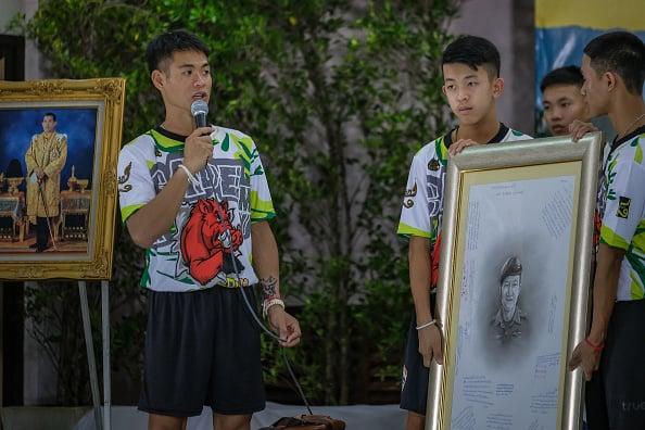 7月18日,泰國小足球隊教練Ekkapol Chantawong (左)和他的球隊成員,一起向為營救他們犧牲的泰國前海軍海豹突擊隊員致敬。(Linh Pham/Getty Images)