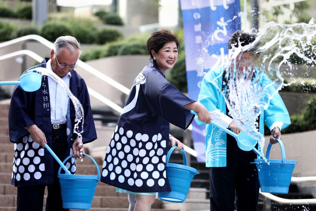 7月23日,東京都知事小池百合子在高溫中,與民眾一起用水潑街來降溫。(Behrouz MEHRI/AFP/Getty Images)