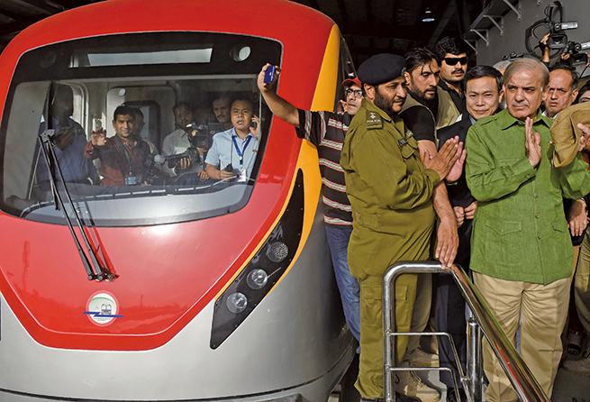 2018年5月中共投資的橙線地鐵在巴基斯坦Lahore首次測試營運,旁遮普省首席部長Shahbaz Sharif(前右一)到場。其身邊及駕駛室內都有中方人員。(AFP/Getty Images)