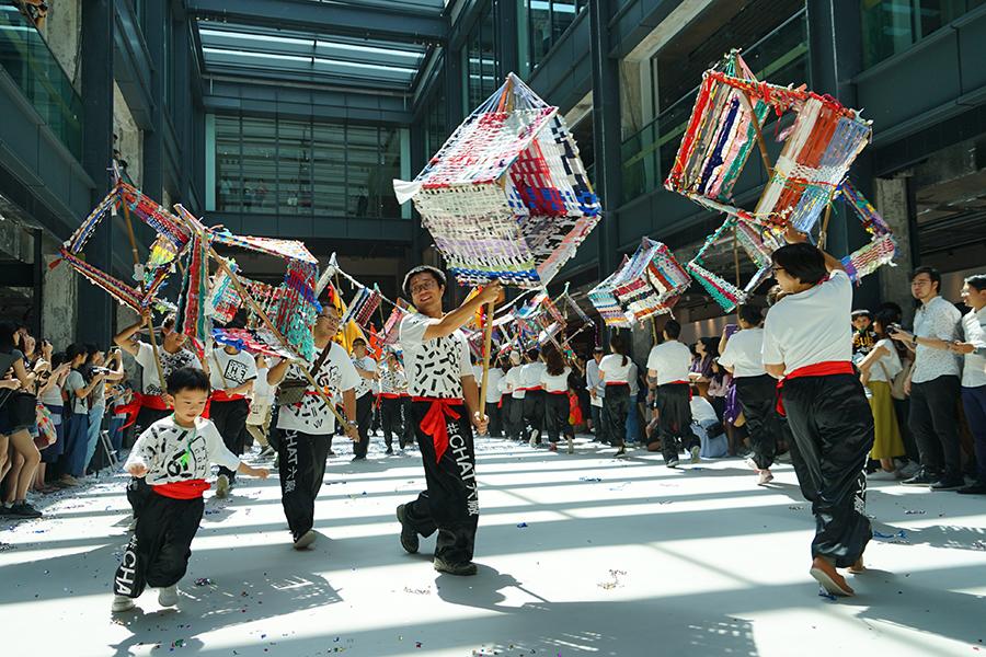 田口行弘和吳師傅帶領一眾荃灣街坊和學生在開幕禮上舞動紡織龍。(曾蓮/大紀元)