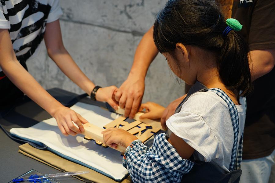 本地紡織創作人指導小朋友進行木板印刷染上花紋圖案。(曾蓮/大紀元)