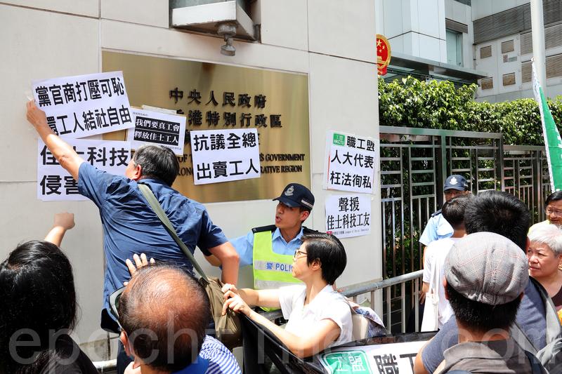 由於中聯辦不肯接信,示威人士將抗議信和標語貼到中聯辦的門牌上。(李逸/大紀元)