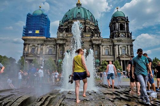 2018年8月4日,隨著歐洲持續熱浪,柏林溫度達到33攝氏度,民眾走在柏林大教堂前的噴泉中消暑。(AFP)