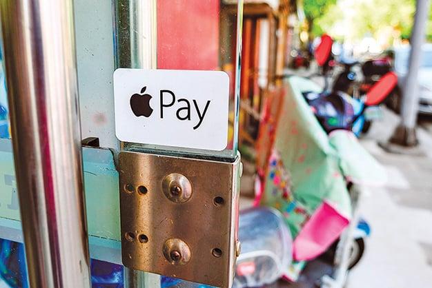 蘋果公司Apple Pay已經普及到二十多個國家,圖為一家商店外的Apple Pay標識。(shutterstock)