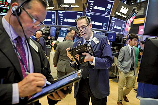 美國財經新聞CNBC日前發表文章,分析了為甚麼美國股票市場沒有受到貿易戰等不穩定因素的影響,而直逼史上最高紀錄。(Drew Angerer/Getty Images)