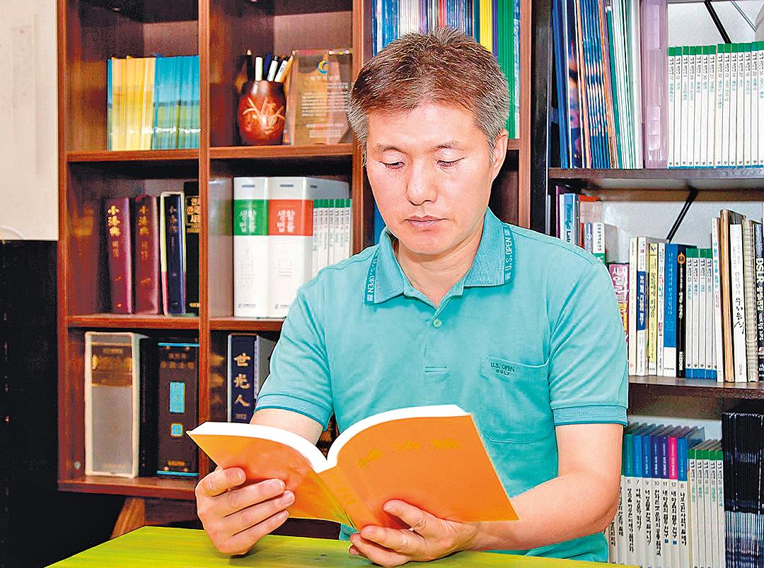 韓國資深律師李惇榮在讀法輪大法主要書籍《轉法輪》。(明慧網)