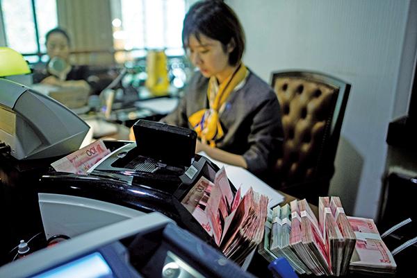 有專家表示,隨著美中貿易戰升級,美國總統特朗普可能將中共列為貨幣操縱國。圖為2018年8月8日,上海一家銀行的職員在清點人民幣鈔票。(AFP)