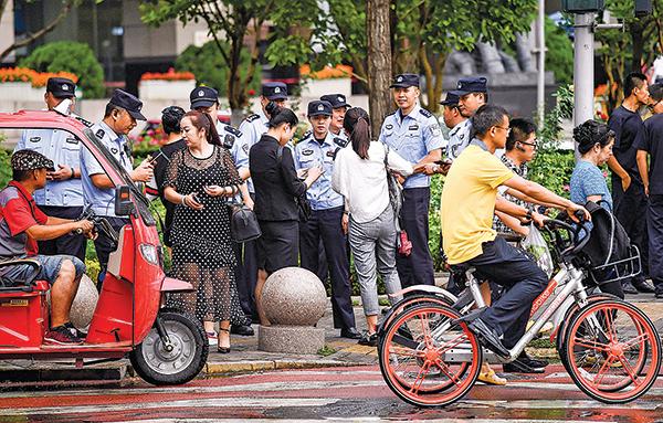 因在P2P融資平台上遭受損失,各地訪民進京上訪。圖為8月6日數百名警察在北京金融區的街道上監控訪民。(AFP)