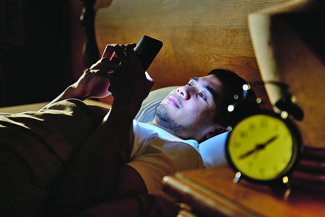 專家建議人們不要在黑暗中查看電子設備,這樣會減少藍光對眼睛的損害。(shutterstock)