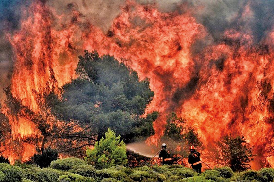 在極端高溫天氣下,2018年7月24日希臘雅典附近的Kineta村發生森林大火。圖為消防員正試圖撲滅肆虐的火焰。(AFP)