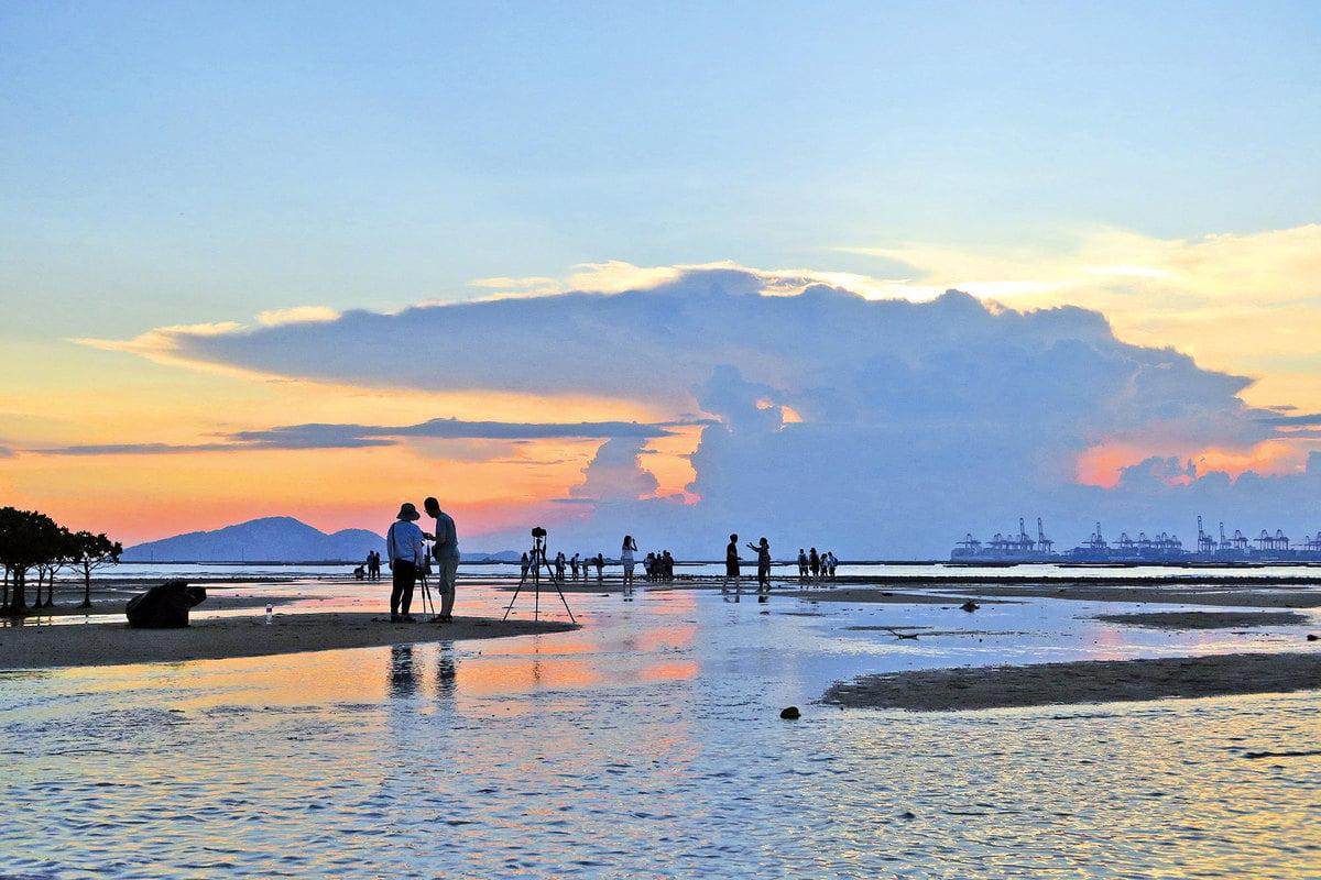 黃昏漸近,泥灘上的水漥也反映出晚霞的色彩,如詩如畫。
