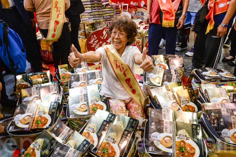 75歲陳婆婆參加遊戲贏得26盒鮑魚。(宋碧龍/大紀元)