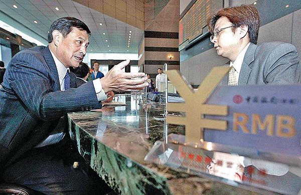 一名客戶與中國大陸某銀行經理商談人民幣兌換業務。(Getty Images)