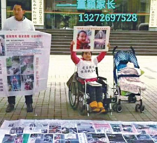 坐在輪椅上董穎和她的爸爸董傑,以及一對4個月大的雙胞胎妹妹在重慶市衛計委大門口上訪維權。(受訪者提供)