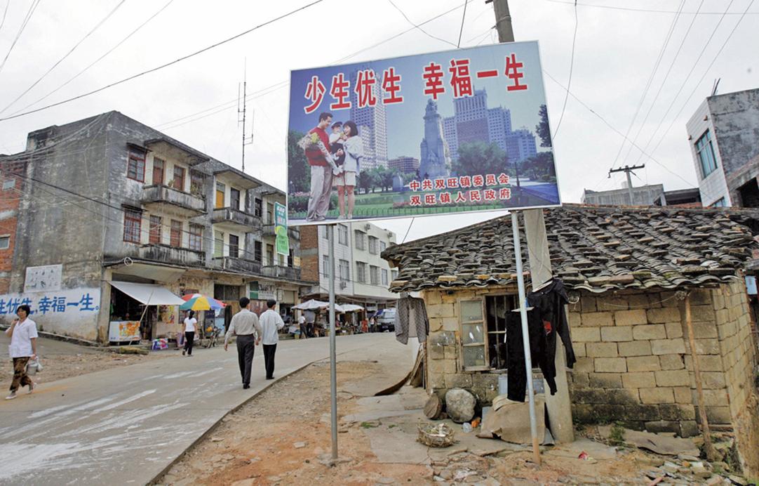 2016年1月,中共政府推行的「二孩」政策。圖為2007年廣西雙旺鎮街道上掛著宣傳計劃生育政策的廣告牌。(AFP)