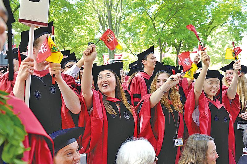 近來很多數據顯示,擁有學位不論在獲得就業,還是在薪資水平上,均好過高中畢業生。圖為2013年哈佛大學的畢業生舉旗慶祝畢業。(Getty Images)