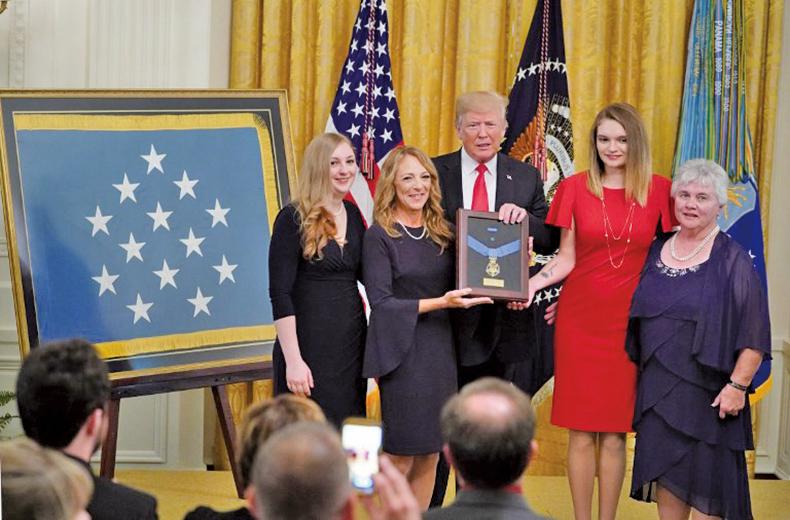 8月22日,美國總統特朗普在白宮東廳向查普曼遺孀頒發榮譽勳章。(AFP)