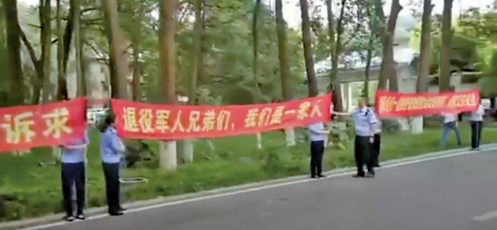 四川綿陽警察打起橫幅,企圖誘勸維權老兵放棄維權。(影片截圖)
