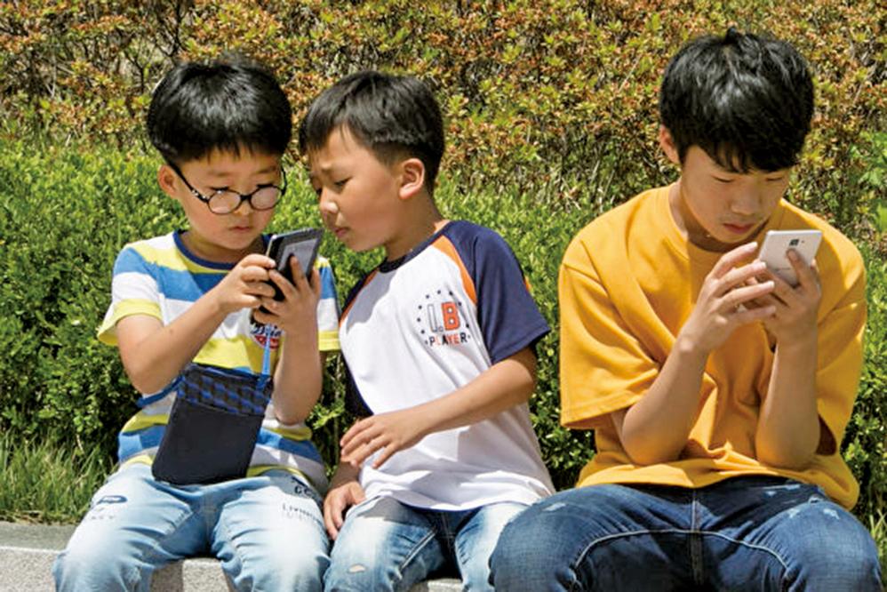 南韓智能手機普及率極高,除了對社會經濟造成一定的積極推動作用,對社會的負面影響也是巨大的。圖為南韓青少年在看手機。(全景林/大紀元)
