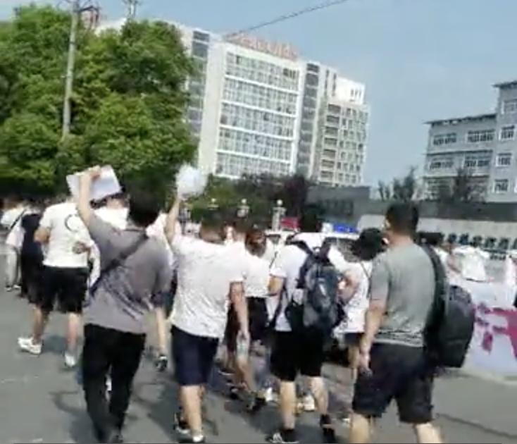 斐訊平台投資受人上街打橫幅遊行,要求還錢。(視頻截圖)