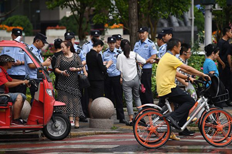 因在P2P融資平台上遭受損失,各地訪民進京上訪維權。8月6日數百名警察在北京金融區的街道上監控訪民。圖為警方檢查路人的身分。(AFP/Getty Images)