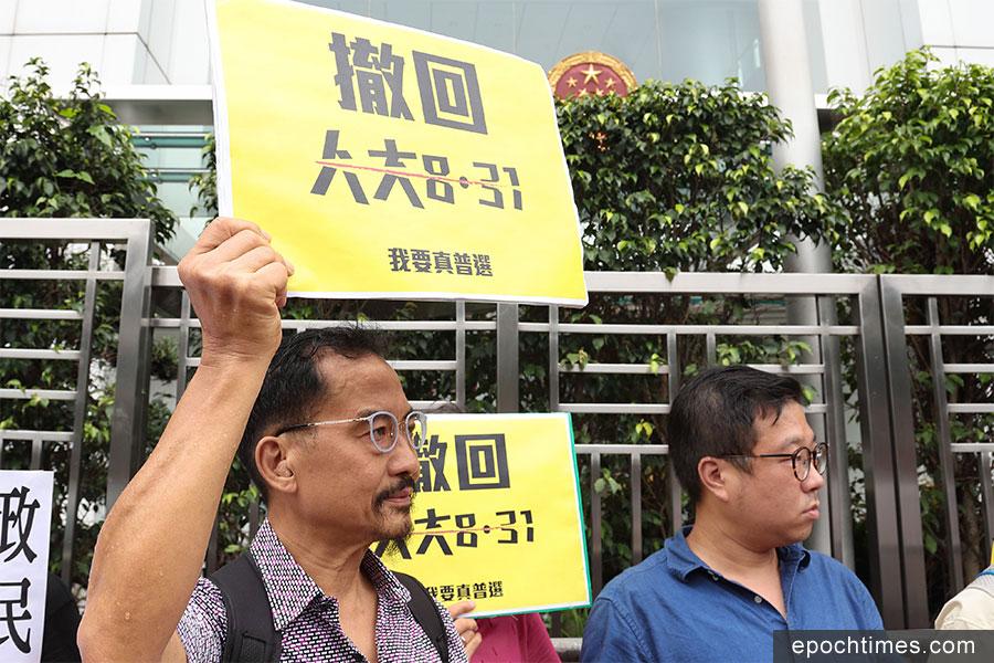 抗議人士在中聯辦前舉起標語,高喊「共產黨找數」、「人大831釋法可恥」、「毋忘雨傘運動」等口號。(潘在殊/大紀元)