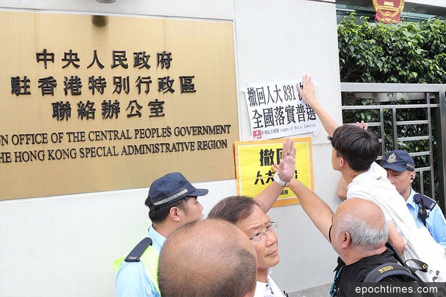 抗議人士將簽名等信件貼在中聯辦門牌上。(潘在殊/大紀元)