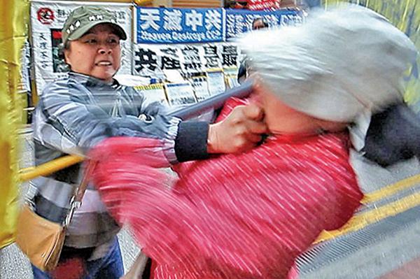 2014年3月22日,法輪功學員李小姐(右)在銅鑼灣法輪功真相點遭親共青關會女成員陶桂香(左)揮拳毆打。陶隨即倒地誣告李小姐打人。(大紀元資料室)