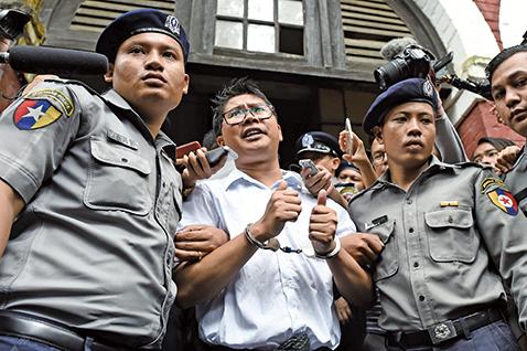 被判刑的記者瓦隆步出法院,向世界各地記者及群眾豎起大拇指,表達堅持新聞自由的決心。(AFP)