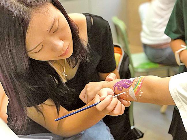 825青年市集,義工為小朋友手部彩繪。(受訪者提供)