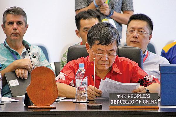 中共代表杜起文(紅衣)在論壇上試圖搶在其他島國元首前發言,被瑙魯總統瓦卡制止。(AFP)