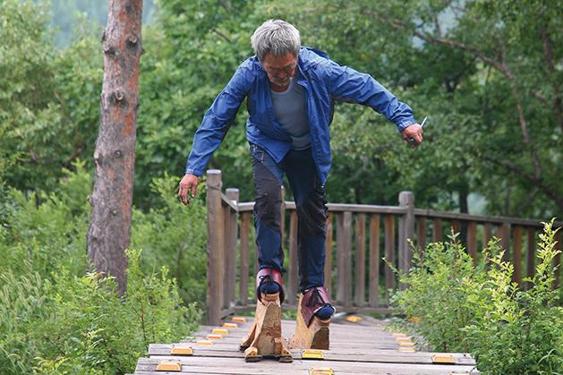 吉林延吉70歲老人穿著自製的16斤重木鞋在鍛鍊。(大紀元資料室)