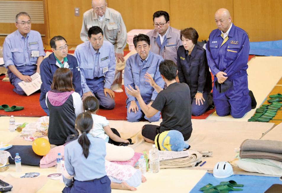 日本首相安倍晉三9日前往災區視察,也向災民保證會「盡全力」重建受創區域。(AFP)