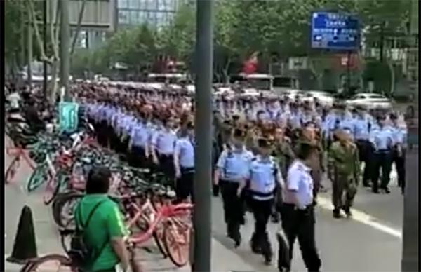 成都老兵向省政府前進,隊伍被大批警察緊張包夾,被網民戲稱為「維權三文治」。(影片截圖)