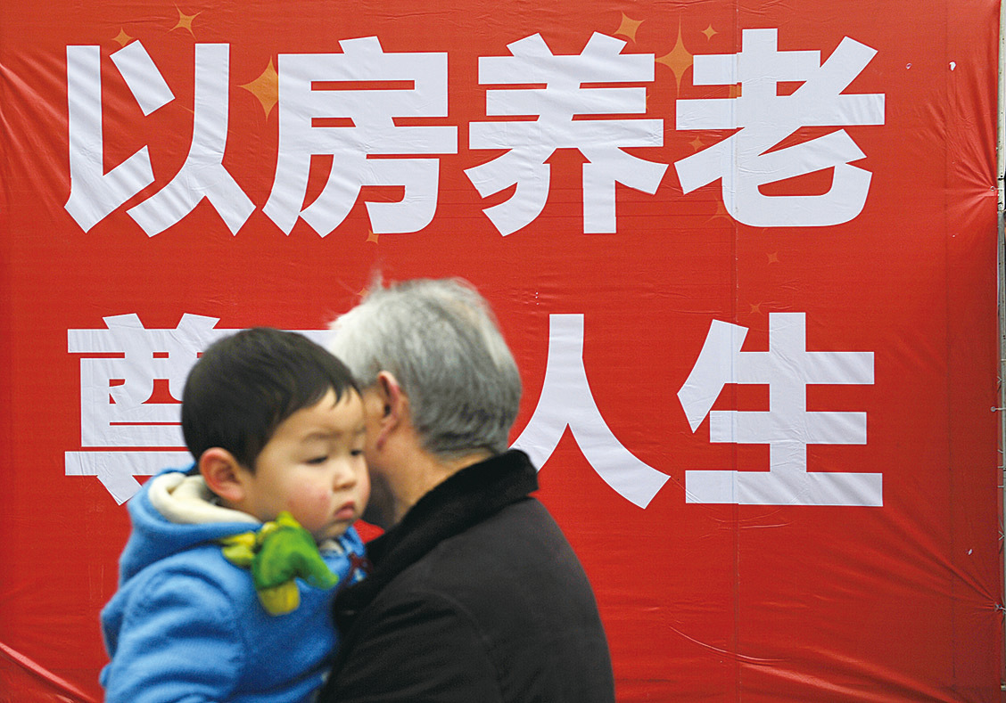 近期,中共提出的「以房養老」政策即將全國推行。圖為老人路過宣傳標語。(大紀元資料室)