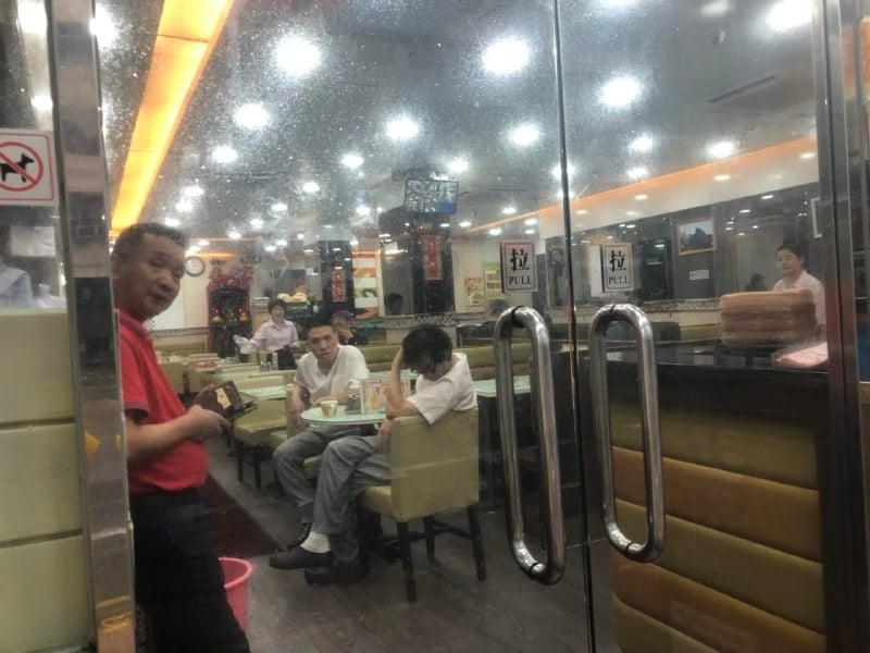 餐廳內有熟客正在用膳,馬老闆(紅衫)指沒有加價。(梁珍)