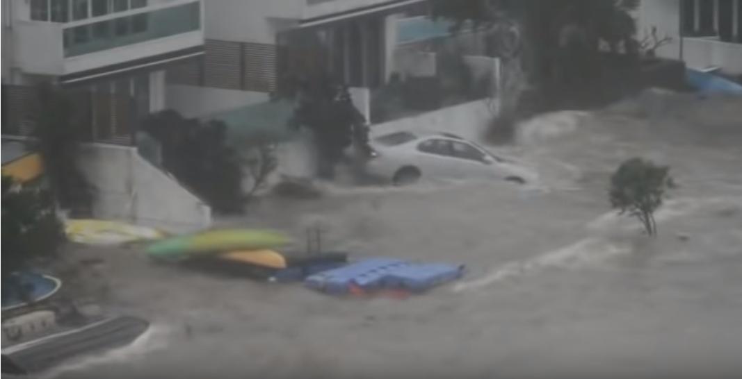 「山竹」吹襲,香港沿岸地區都被勁風巨浪襲擊。匡湖居被急升的海水淹浸,停泊在屋前的私家車變成小船,隨浪漂動。(影片截圖)