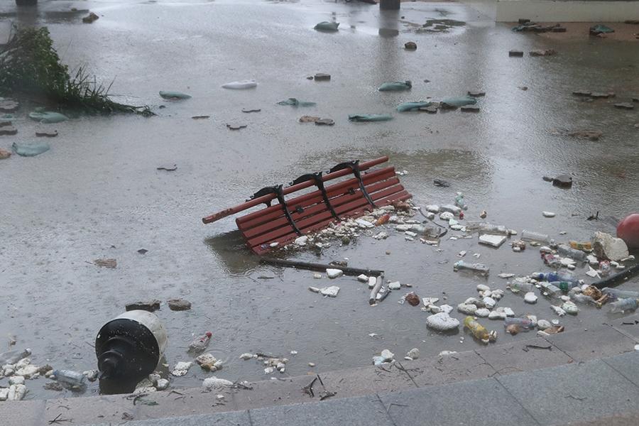 杏花邨海邊長凳被強風吹折斷,周圍漂浮著垃圾。(陳仲明/大紀元)