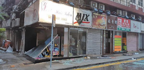 西灣河聖十字徑有店舖玻璃門破碎,散落一地。(讀者提供)