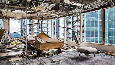 紅磡海濱廣場二期大量玻璃幕牆被颱風吹毀,辦公室內猶如災難現場。(Getty Images)