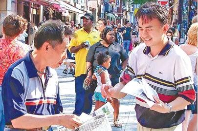 來到加拿大的王曉華獲得了自由修煉法輪功的權利。圖為王曉華(右)在唐人街向民眾發放法輪功真相資料。(大紀元資料圖片)