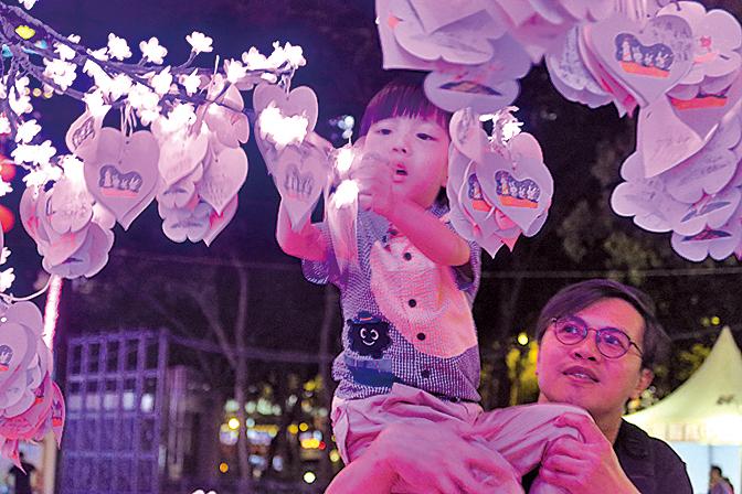 圖為去年維園綵燈會設置了兩棵人造桃花樹,供遊客及市民掛上寫上願望的心意咭。(大紀元資料圖片)