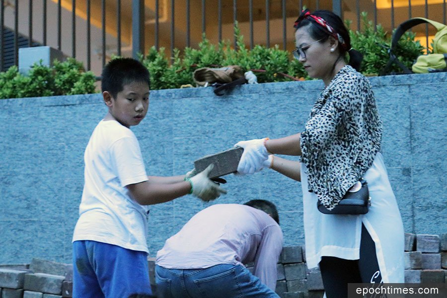 黃同學(左)表示參與清理行動有些成就感,因為可以幫到社區重建。(陳仲明/大紀元)