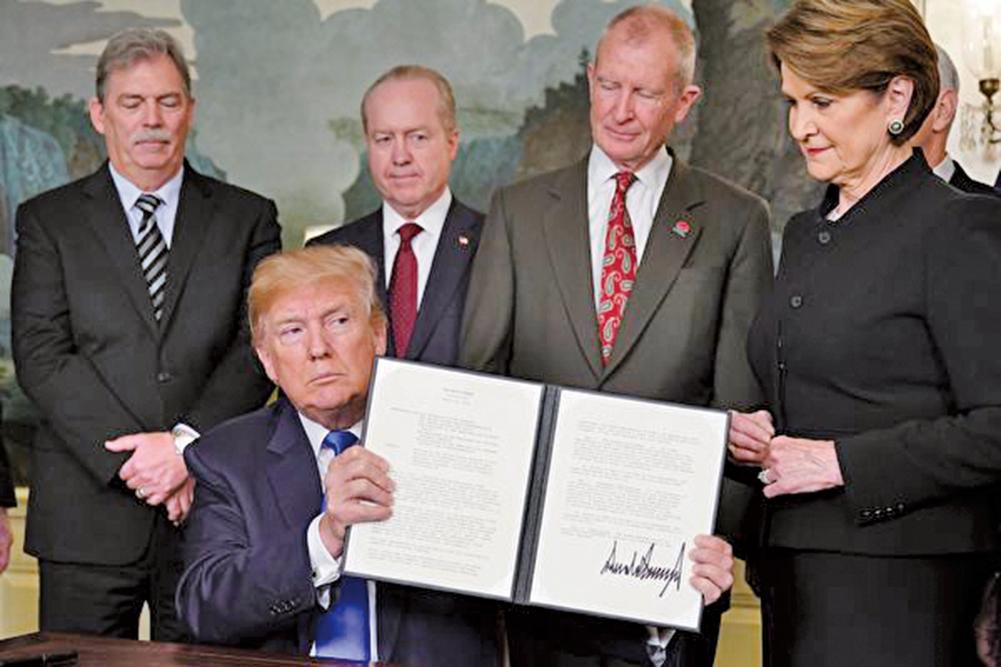 圖為美國總統特朗普今年3月簽署301備忘錄,開啟中美貿易關稅之戰。(AFP)