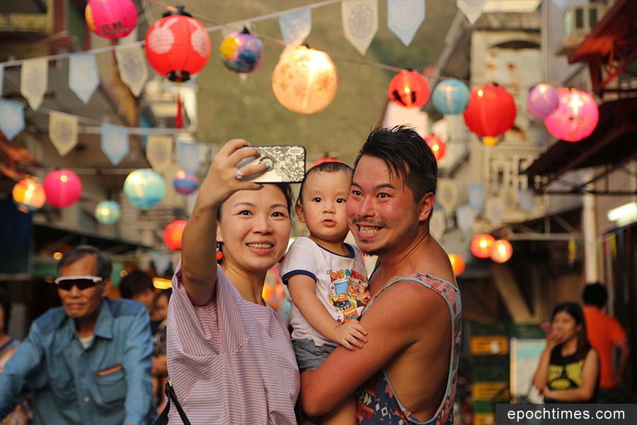遊客與大澳吉慶街的手繪燈籠合照。(陳仲明/大紀元)