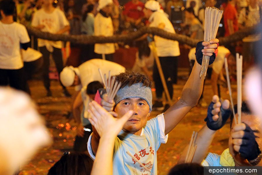 火龍補香時,工作人員從火龍身上取下香燭,把火種熄滅,再分發給現場的觀眾,寓意保祐平安。(陳仲明/大紀元)