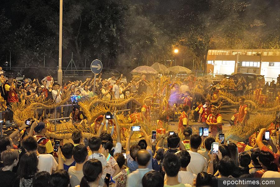 大龍抵達華富邨進行補香期間,市民紛紛舉起手機拍攝象徵吉祥的火龍。(曾蓮/大紀元)